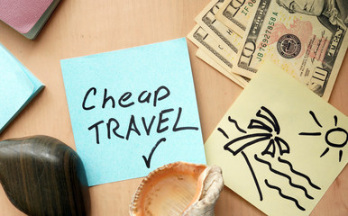Cheap travel paper on a table with money