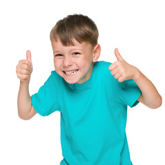 Laughing little boy holds his thumbs up
