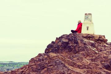 Girl enjoying view of Edinburgh from top of Arthurs seat, UK