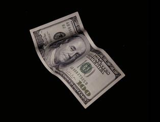 Billete de cien dólares cayendo sobre fondo negro.