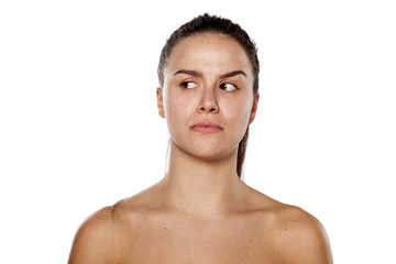 jealous young woman without makeup looking aside