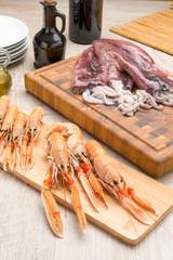 Calamari e scampi crudi su taglieri di legno