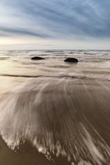 Sunrise dawn landscape on rocky sandy beach with vibrant sky and
