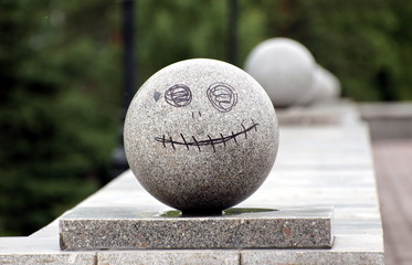 granite ball with painted on it with a smile and eyes