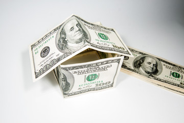 house built with $ 100 banknotes on a white background