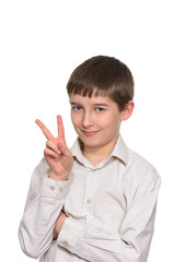 Portrait of happy boy showing victory fingers isolated over whit