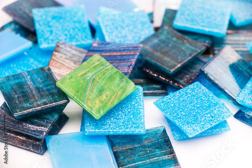 Stack of blue and green glass mosaic tiles on white background - 79439115
