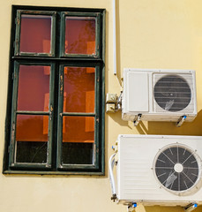 Air conditioners on the wall next to a window