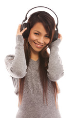 Asian woman is listening music with headphones over white isolat