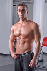 Hombre fuerte musculoso entrenando en un gimnasio.