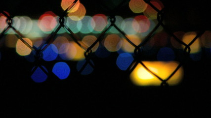 Out of focus lights flicker behind a chain-link fence near an airport. The lights of the run way twinkle in the background.