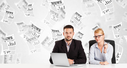 Business man and woman at desk with stock market newspapers