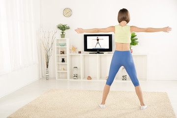 Young Woman Exercise In Front Of TV