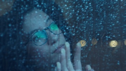 Bored girl behind window in a rainy day. Shot in slowmotion