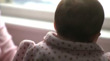 A two month old infant looking out a window.