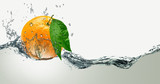 Orange with green leaves on a background of splashing water.