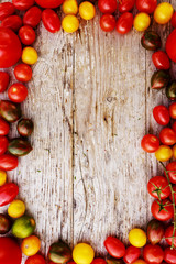 Frame of tomatoes family varieties over a rustic wooden backgrou