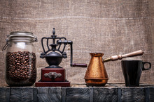 Coffee beans in a glass jar, coffee grinder, a coffee pot, a mug
