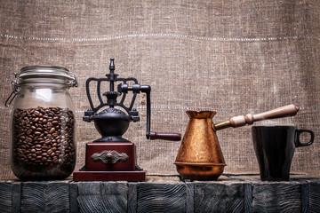 Coffee beans in a glass jar, coffee grinder, a coffee pot, a mug