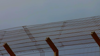 Metal fence on a cloudy sky background. Time lapse