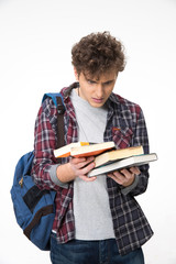 Amazed young man with books over gray background