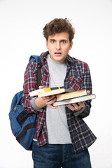 Surprised young man with books over gray background