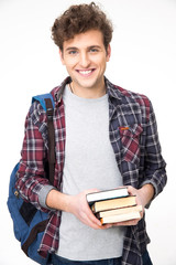Happy young man with backpack and books over gray background