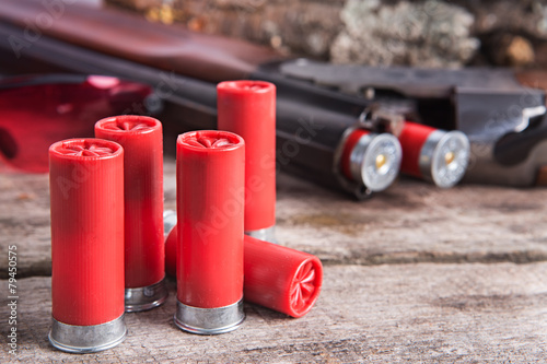 12 gauge shotgun shells with shotgun on wood surface - 79450575