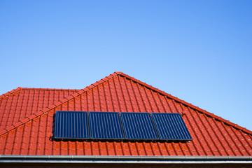 Solarkollektoren für Warmwassergewinnung auf rotem Dach