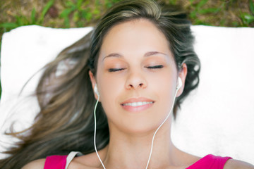 Woman relaxing on the grass while listening music