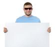 Bearded man in sun glasses holding white billboard