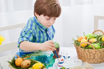 The day before Easter, beautiful child painting eggs for easter