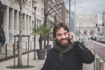 Young handsome bearded man talking on phone