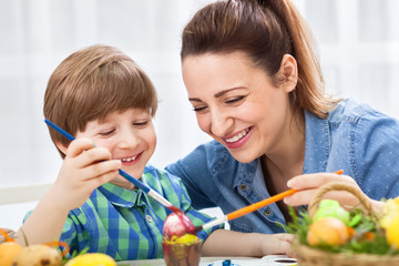 Smiling happy mother and child enjoy in painting easter eggs