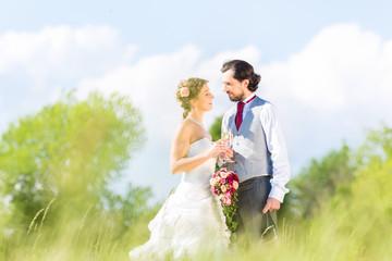 Hochzeitspaar feiert draußen Hochzeitstag mit Sekt