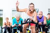 Fototapeta Senioren beim Spinning auf Fitness bike mit Trainer