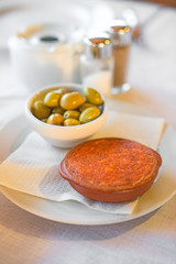 Sobrassada with olives on a table in restaurant.