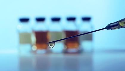 Needle of syringe with ampules on blue blurred background