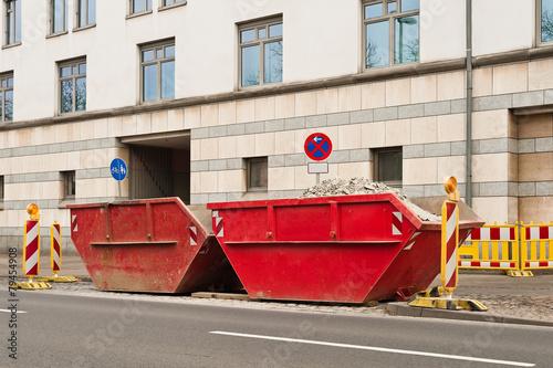 Zwei rote Container für Bauschutt stehen am Strassenrand