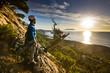 rock climber standing near tree looking on sunrise