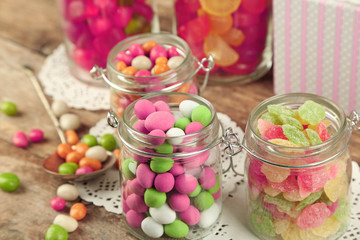 Multicolor candies in glass jars on wooden background