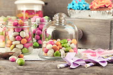 Multicolor candies in glass jars and cupcakes