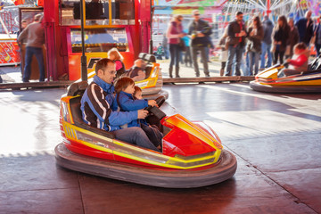 Father and his two sons,l having a ride in the bumper car at the