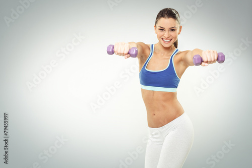 Beautiful young woman exercise with dumbbells on white backgroun
