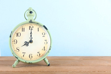 Alarm clock on wooden table on light background