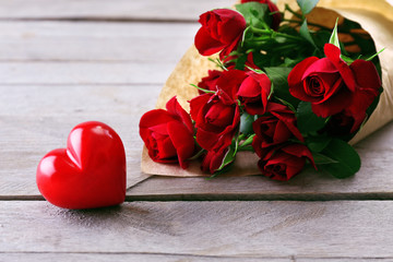 Red roses wrapped in paper with heart on wooden table