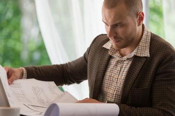 Happy businessman working with blueprint