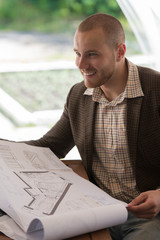 Happy businessman working with blueprint