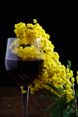 Bicchiere vino rosso con mimosa festa della donna