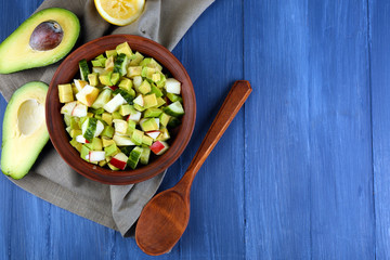 Salad with apple and avocado in bowl with napkin